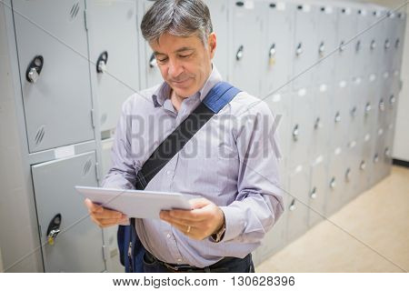 Professor using a digital tablet in locker room at university