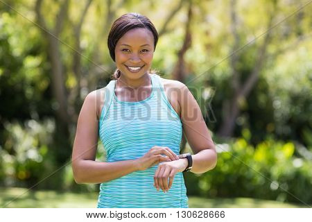 Happy woman posing and touching her watch