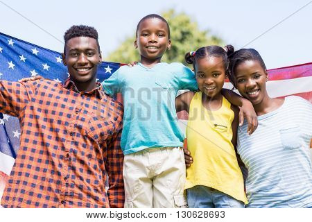 Happy family showing usa flag at park