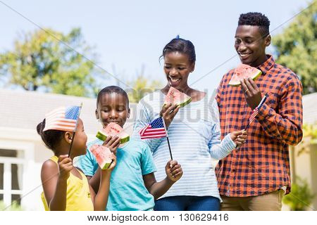 Happy family eating watermelon and showing usa flag at park