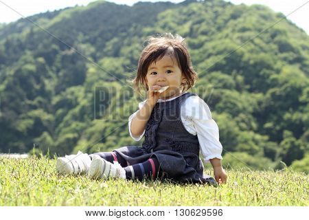 Japanese girl eating rice cracker (1 year old)