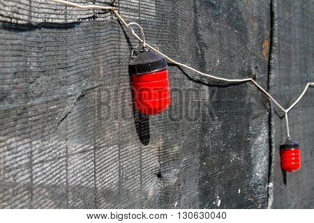 Red warning lights on the grey fence