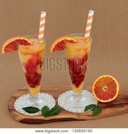 Blood orange fruit juice drink in glasses on doilies with striped straws on an olive wood board over ridged brown paper background. High in vitamins, anthocyanins and antioxidants.