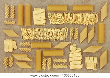 Pasta selection forming an abstract background over natural hemp paper background.