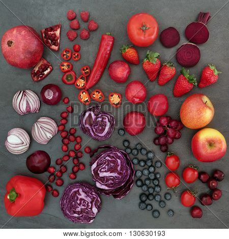 Red and purple health food with a selection of fruit and vegetables,  high in vitamins, anthocyanins antioxidants and dietary fiber over slate background.