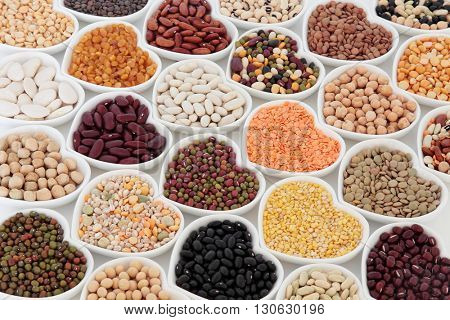 Dried vegetable pulses health food selection in heart shaped porcelain china dishes over white background.
