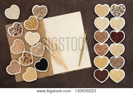 Natural grain health food selection in heart shaped bowls with a hemp paper notebook, wheat sheaths and old pen over lokta paper background.