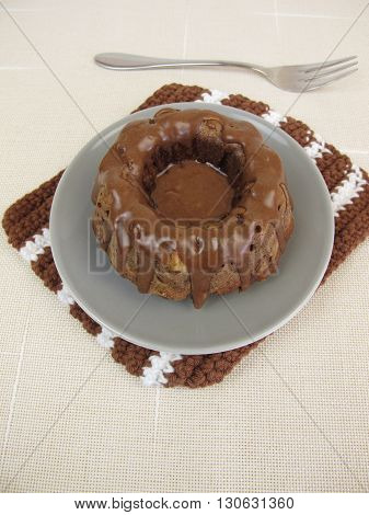 Homemade chocolate gugelhupf with chocolate icing on plate