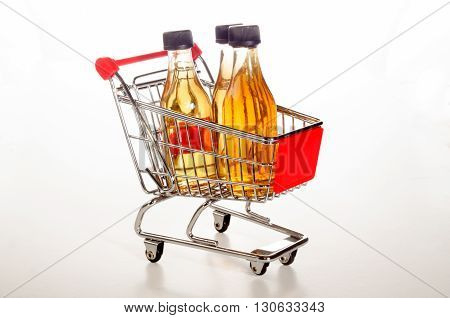 shopping trolley with filled apple juice bottles on bright background