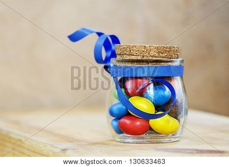 colorful candies jelly beans in a jar tied with a blue ribbon
