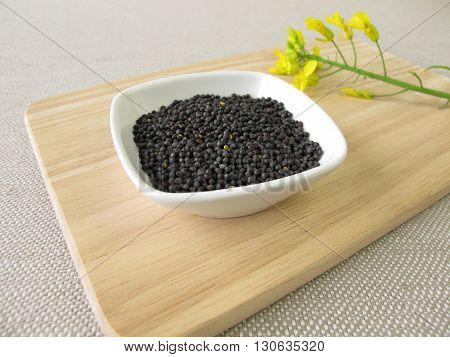 Rapeseeds for canola oil in small bowl on wooden board