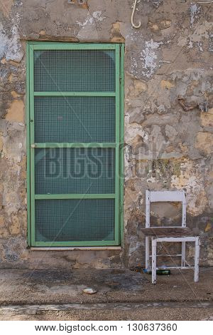 One of the weekend houses in a fishing village at the island Malta. Old stone walls green door. Old white empty chair.