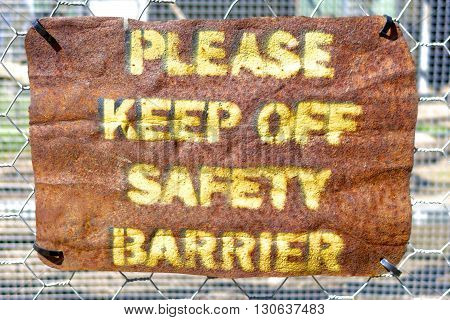 Please Keep off Safety Barrier sign in rough letters.