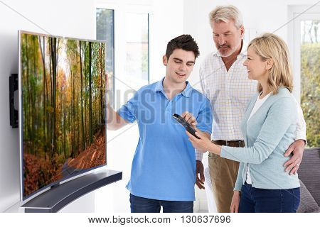 Man Demonstrating New Television To Mature Couple At Home