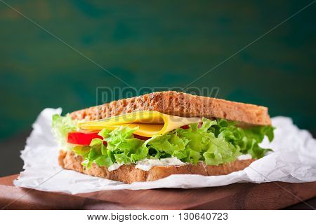 Toasted sandwich with salad leaves tomatoes and cheese with fork on a cutting board on a green background with free space for text closeup horizontal