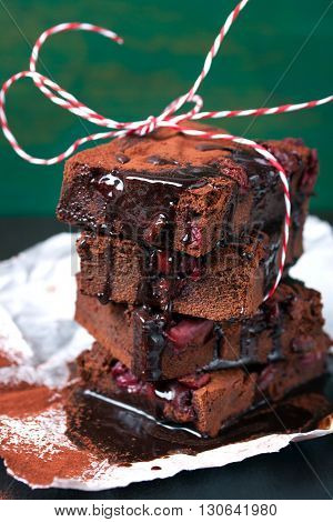 Homemade chocolate sweet brownies cakes with cherry and chocolate sauce or syrup on a dark background closeup