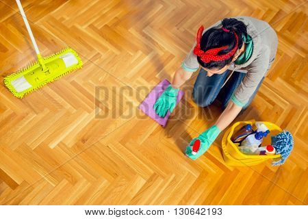 Young woman cleaning floor at home. View from above. Selective focus