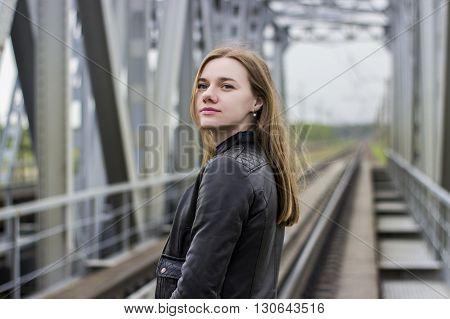 Young beautiful girl walking near railway tracks where the trains run