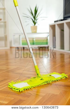 Cleaning the floor with a mop in the living room