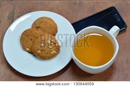 peanut cookie and cup of tea with black cell phone