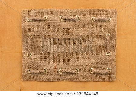 Frame of burlap lying on wooden can be used as texture