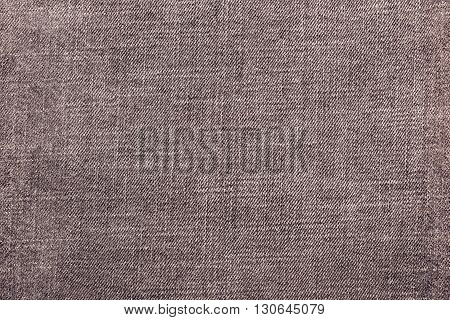 the textured background from rough cotton material or denim of pale brown color