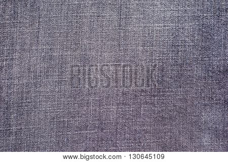 the textured background from rough cotton material or denim of pale violet color