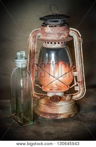 Old rusty burning lamp and a bottle of kerosene on the burlap background.