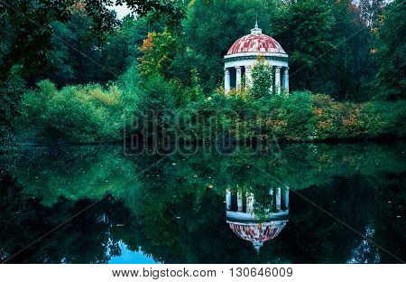 White gazebo rotunda with round dome on a shore of the pond in summer green park.