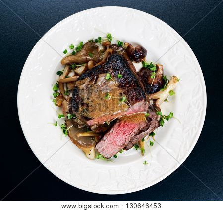Tasty Beef Mignon sliced steak with mushrooms and herbs on plate