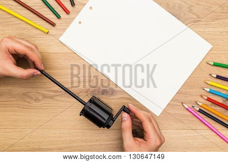 Top view of man's hands sharpening black pencil on wooden desktop with blank white paper sheet. Mock up