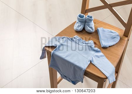 Blue baby apparel on wooden chair, close up
