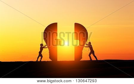 Businesspeople silhouettes putting lightbulb parts together at sunset. Concept of idea and partnership
