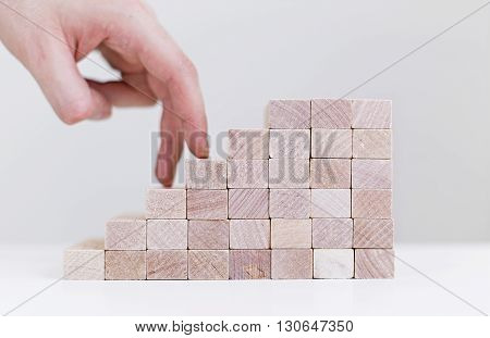 Success concept with businessman hand climbing wooden block stairs on white background