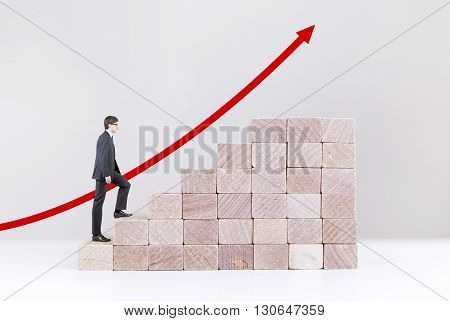 Success concept with businessman climbing wooden block stairs on white background with red arrow going upwards