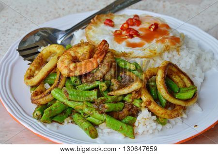 stir-fried curry seafood and fried egg on rice