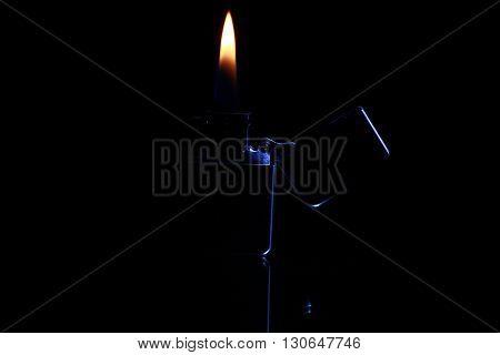 black gasoline lighter with flame on dark background