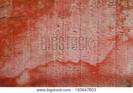 Red wooden board unevenly painted. Wood surface