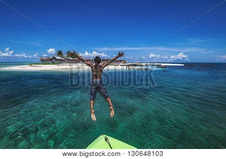 A shot of a person jumped off a boat into a clear water ocean.