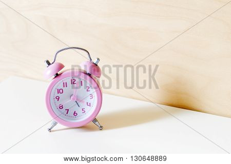 the pink analog alarm clock with the wooden background