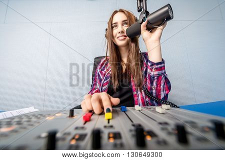female dj working in front of a microphone on the radio