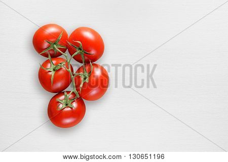 Ripe tomatoes on white table top view