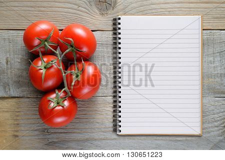 Tomatoes and recipe book on wooden table