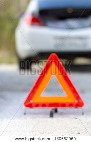 Blurred (out of focus) broken down car and emergency sign