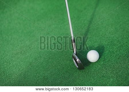 Golf club and ball on a green lawn. Blow to a ball golf club. Golf club and ball close up.