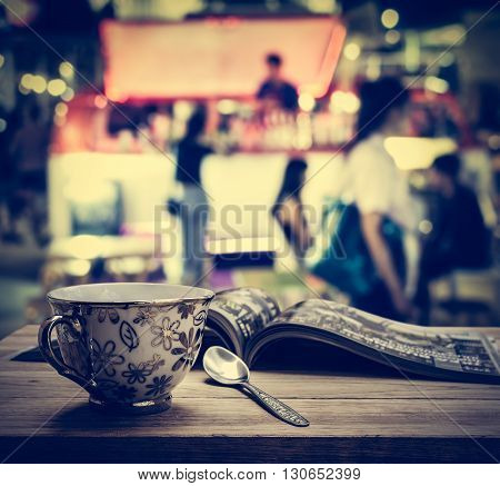 Coffee cup with magazine on wooden table in the night market