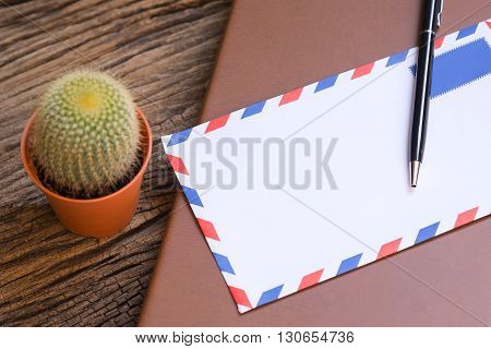 the envelop and the pen and the book on the wooden background table and cactus