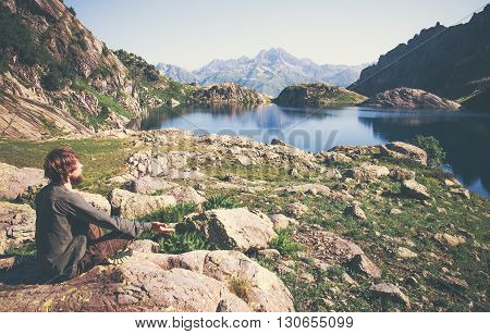 Traveler Man meditating yoga relaxing alone sitting lotus pose on stone Travel healthy Lifestyle concept lake and mountains serene landscape on background outdoor
