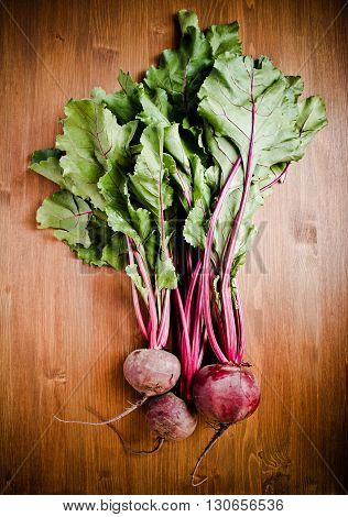 Beetroots with beet tops over wooden background top view