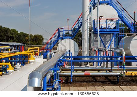 White fuel tanks and color gas pipes in natural gas treatment plant in bright sunny summer day